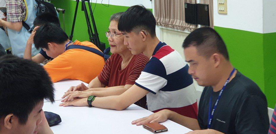 獲得二次師鐸獎的台中啟明學校老師王明理,昨天又回學校,為視障和聽障學生翻譯,在學生手上打點字。記者游振昇/攝影