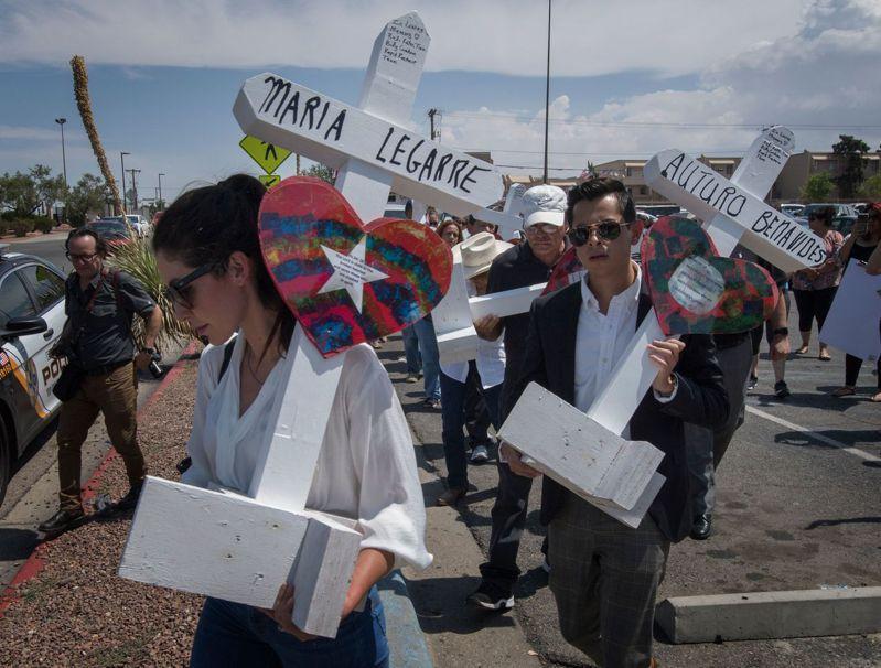 德州民眾舉著十字架,上面寫著槍擊案死者姓名,追悼在艾爾巴索無辜喪生的民眾。 法新社
