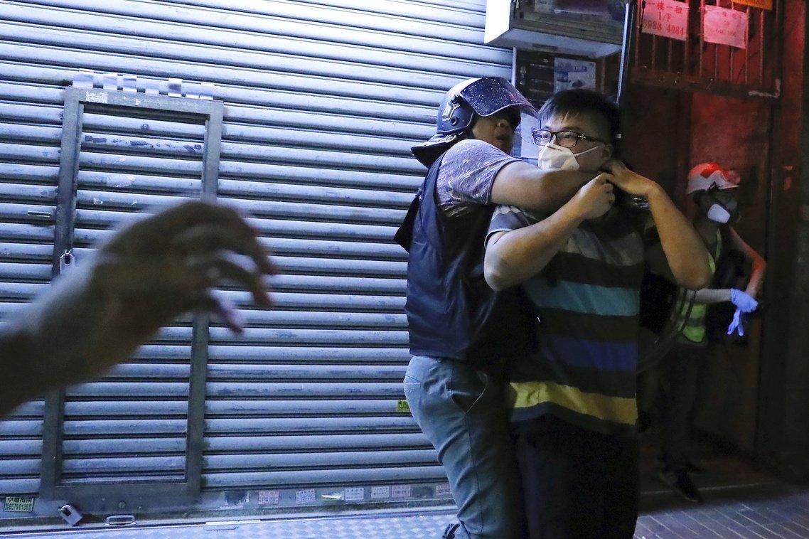 6日深夜,不滿的示威者包圍在警署,要求警方釋放因為購買雷射筆而被捕的方仲賢。圖為...