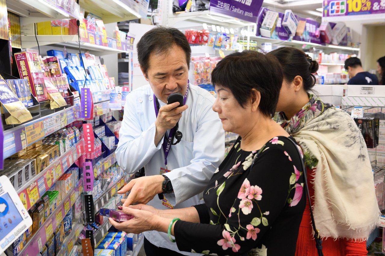 藤田威彥利用翻譯機協助越南來的觀光客選擇商品。 彭博資訊