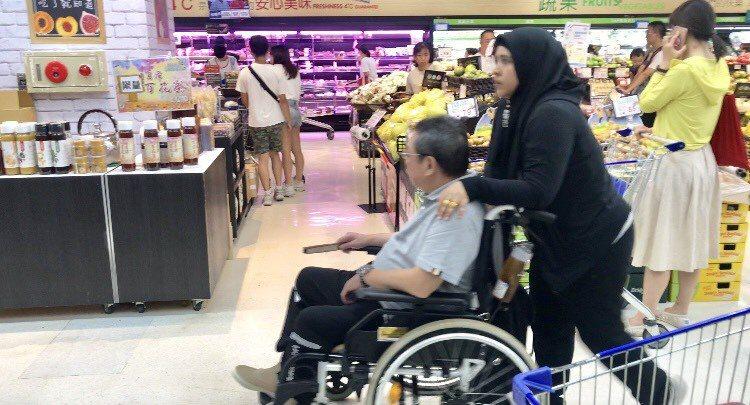陳松勇(左)由印尼看護推著他超市悠晃,輪椅後面掛的不是酒,而是茶壺。記者葉君遠/...
