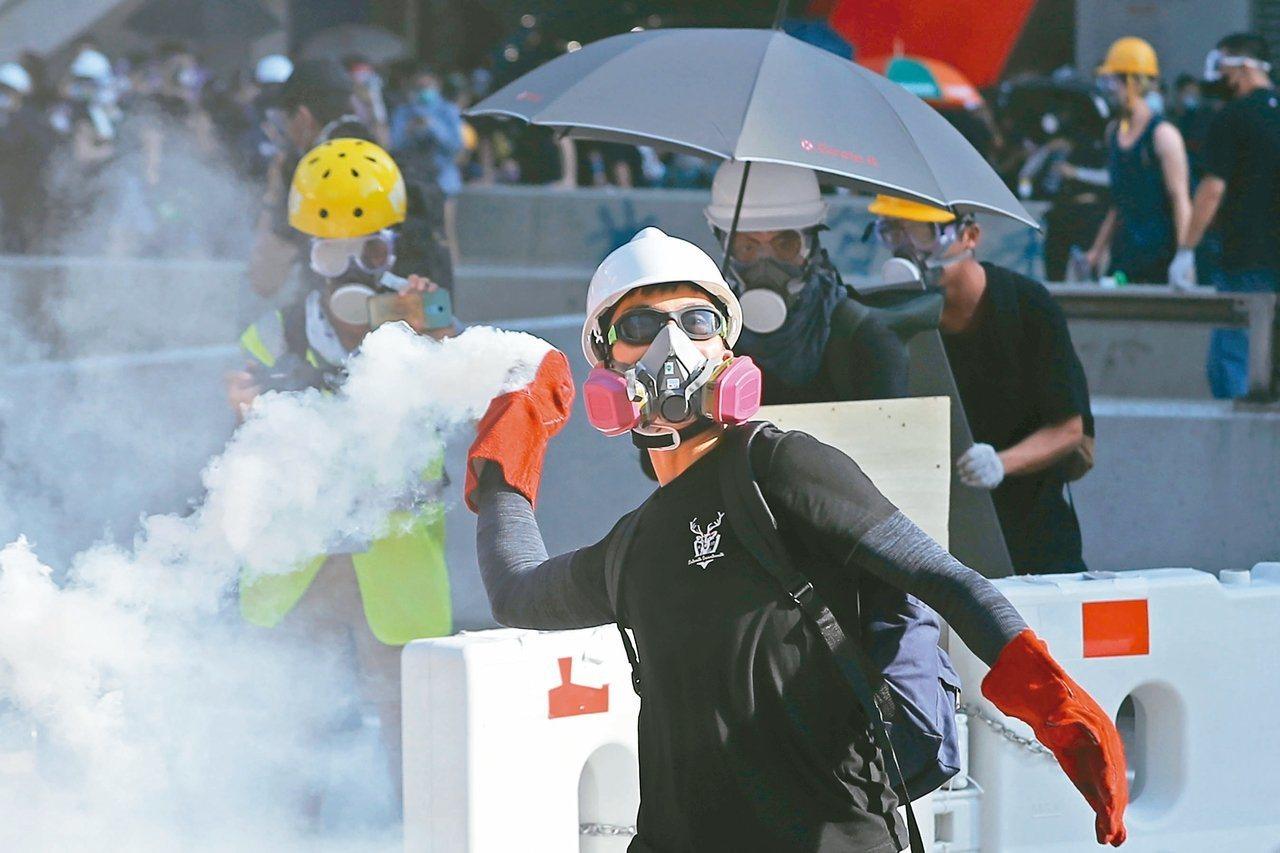 香港反送中抗議持續延燒,一名抗議者試圖將催淚彈丟回給警方。美聯社