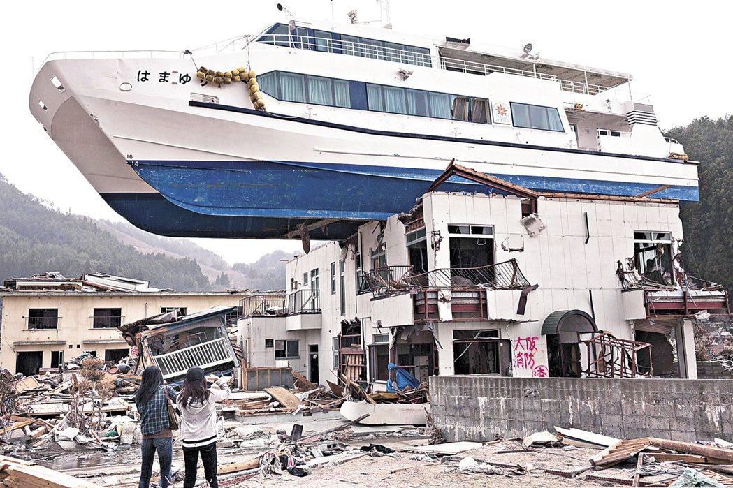 2011年日本發生三一一強震,岩手縣大槌町觀光船被沖至建築物屋頂。 (法新社)