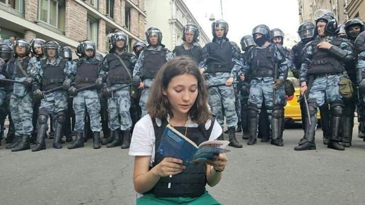 俄羅斯首都莫斯科日前爆發大型示威,警方粗暴逮捕1000多人,一名少女坐在鎮暴警察...