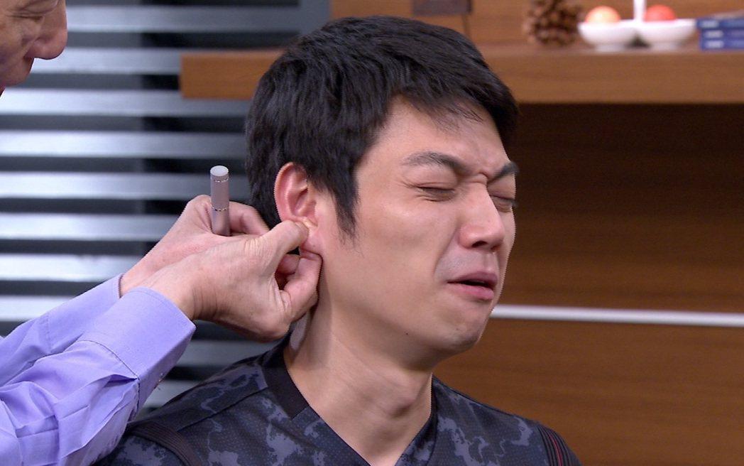 李沛勳被壓耳穴表情痛苦。圖/年代提供