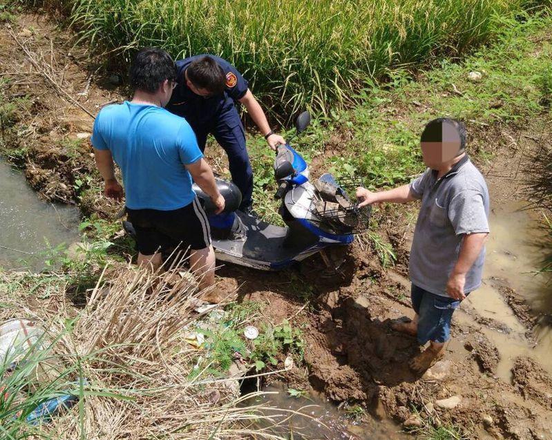 桃園市平鎮區一對父子,趁颱風雨停共乘機車巡視稻田是否災損,一陣強風吹襲而來,倆父子連人帶車落稻田駁坎,受困泥濘田間。圖/平鎮警分局提供