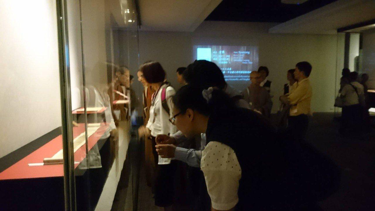 佛光山「穿越時空‧法寶再現」活動開幕,佛經特展中有許多珍貴經典,觀眾認真欣賞。圖...