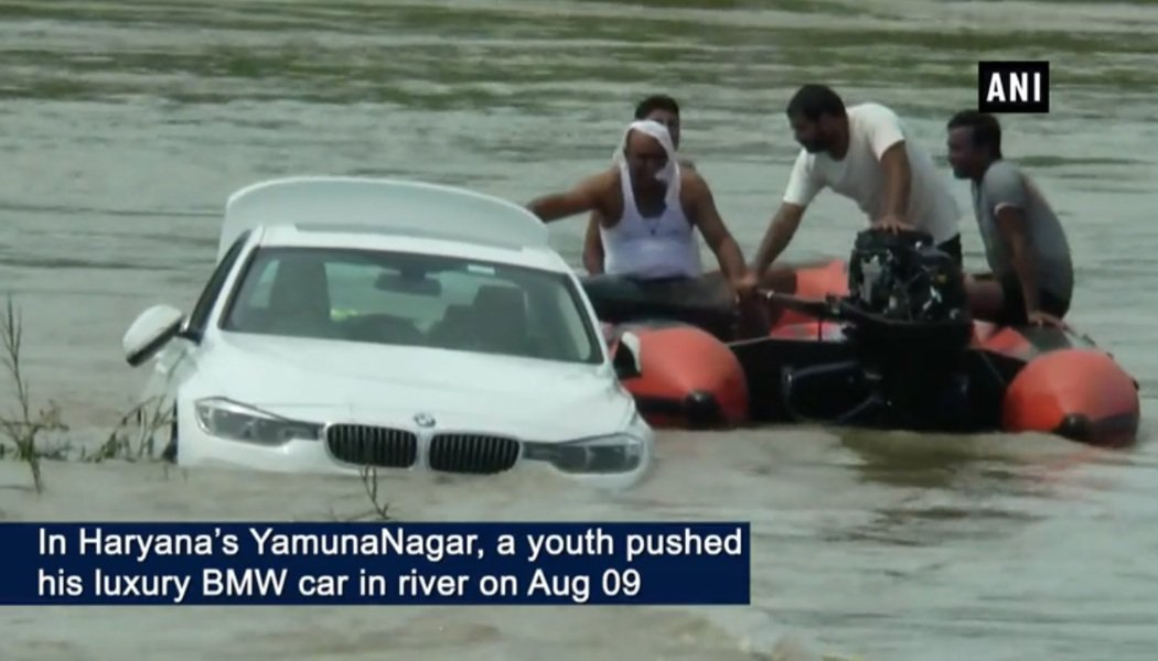 當地民眾合力將河中的BMW轎車拖回岸上。(取自印度時報)