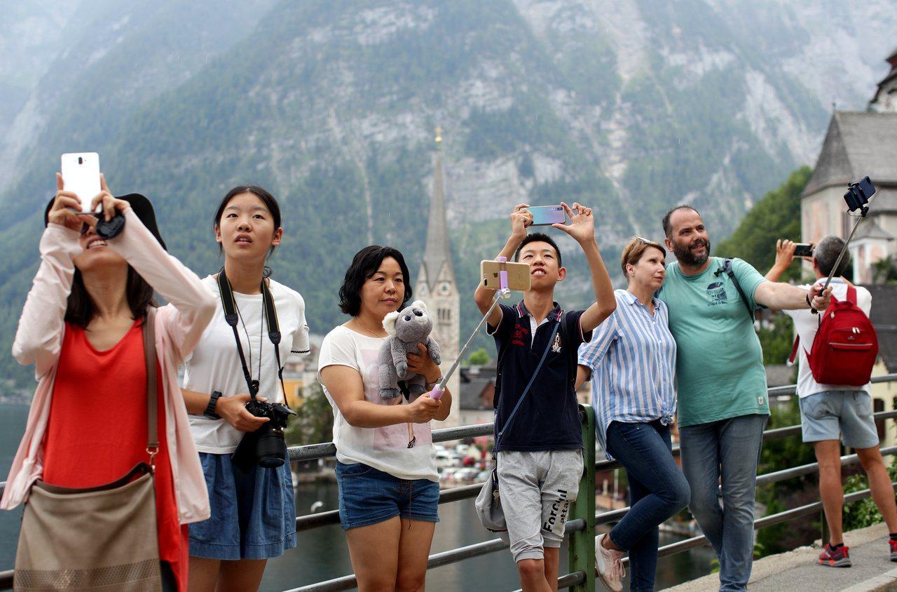 遊客在哈爾施塔特湖畔拍照。 (路透)