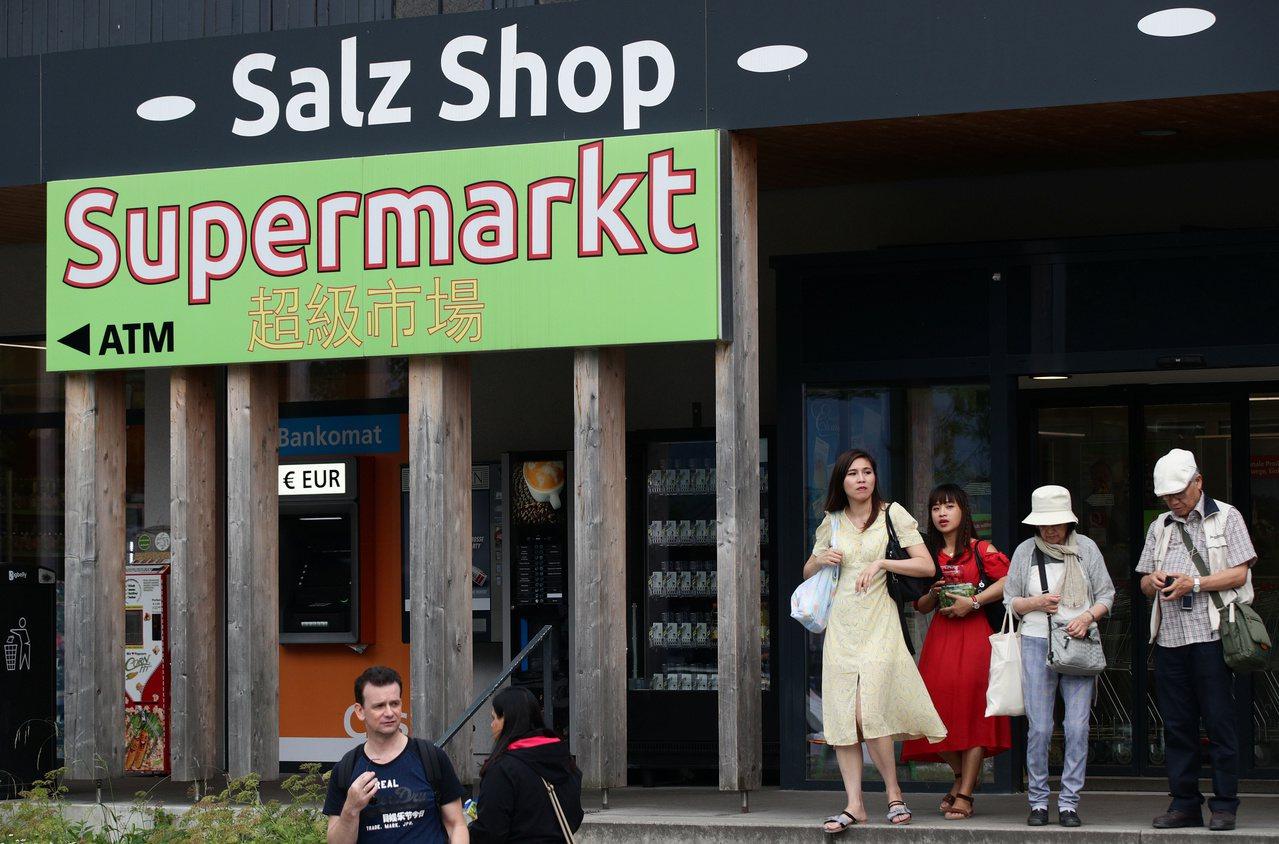 哈爾施塔特一間超市外的遊客。 (路透)