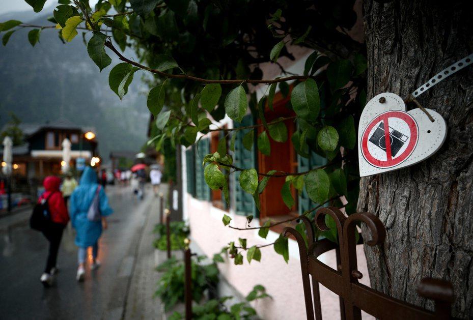 哈爾施塔特一處民宅旁的樹上掛著「請勿拍照」標誌。  (路透)
