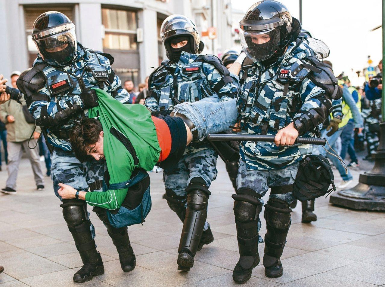 莫斯科10日再度大規模抗議,一名抗議男子被鎮暴警察抬走。 美聯社