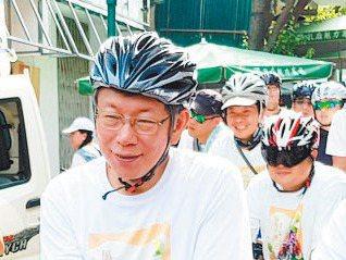 台北市長柯文哲(前)上午南下騎單車拜訪台南市中心十間廟宇。 記者修瑞瑩/攝影