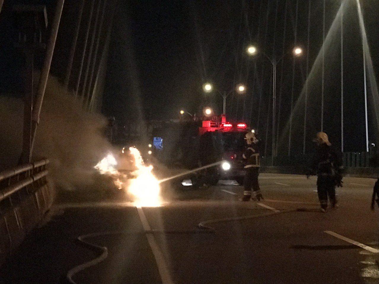 BMW跑車在新北大橋上起火燃燒,消防隊正射水撲滅。記者林昭彰/翻攝