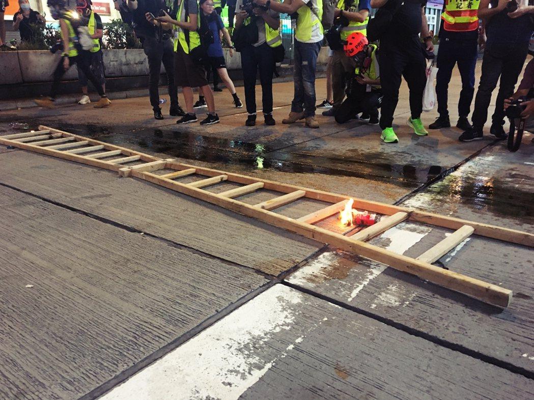 一陣混亂後,示威者重組了防線。兩個木梯子,木梯子前方是一灘油。他們鼓譟,以雨傘柄...