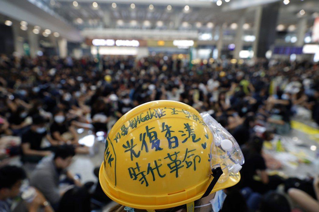 8月9日,一位港人參與機場集會,頭上的安全帽寫著「光復香港、時代革命」。 圖/美聯社
