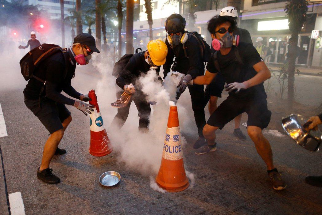 抗爭者用三角錐和水,澆熄煙霧彈。 圖/美聯社