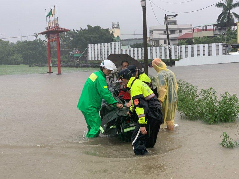 台中市南屯區今天清晨下起大雨,有郵差在中和里中和巷送信時,分不清水面與路面,騎到農田的泥濘當中,動彈不得,警方獲報後提供協助。圖/讀者提供