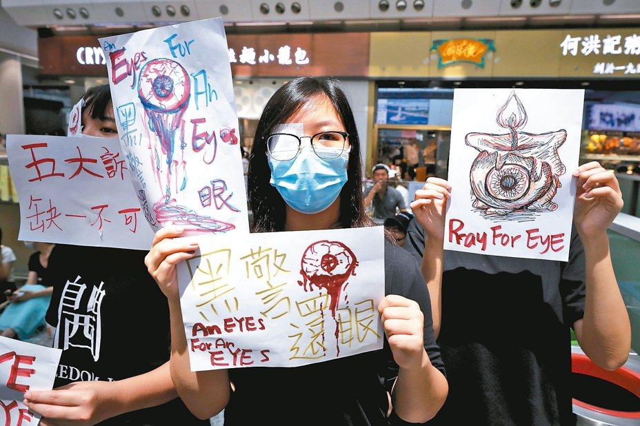 香港示威民眾舉著「黑警還眼」標語,抗議港警疑似發射布袋彈打中一名女示威者眼部。 (美聯社)