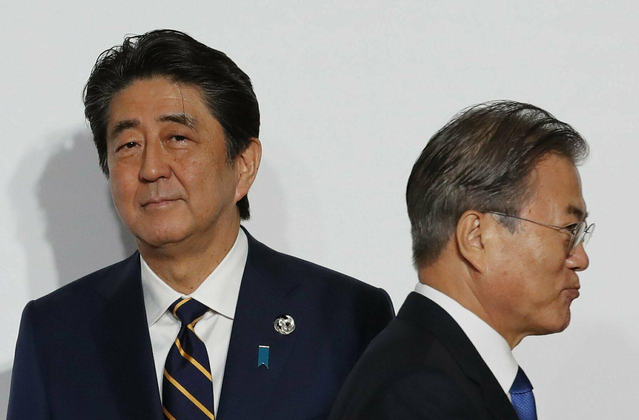 南韓總統文在寅(右)六月底到日本大阪參加G20峰會,走過地主日本首相安倍晉三(左...
