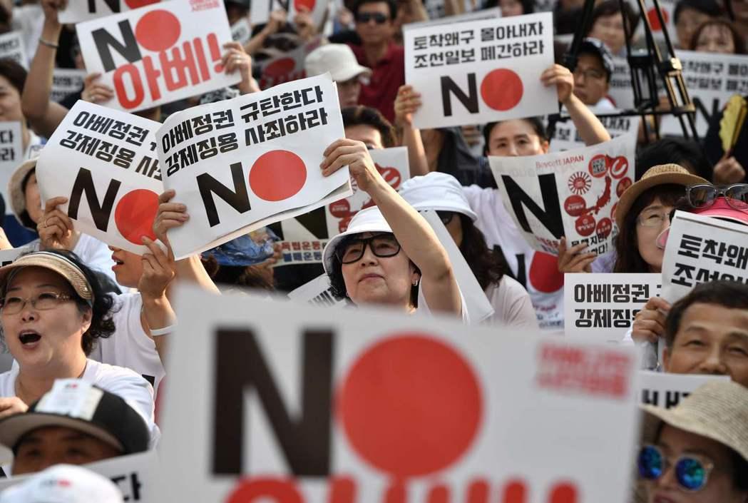 南韓民眾拿著反日標語,抗議日本將南韓移出貿易白名單。 (法新社)