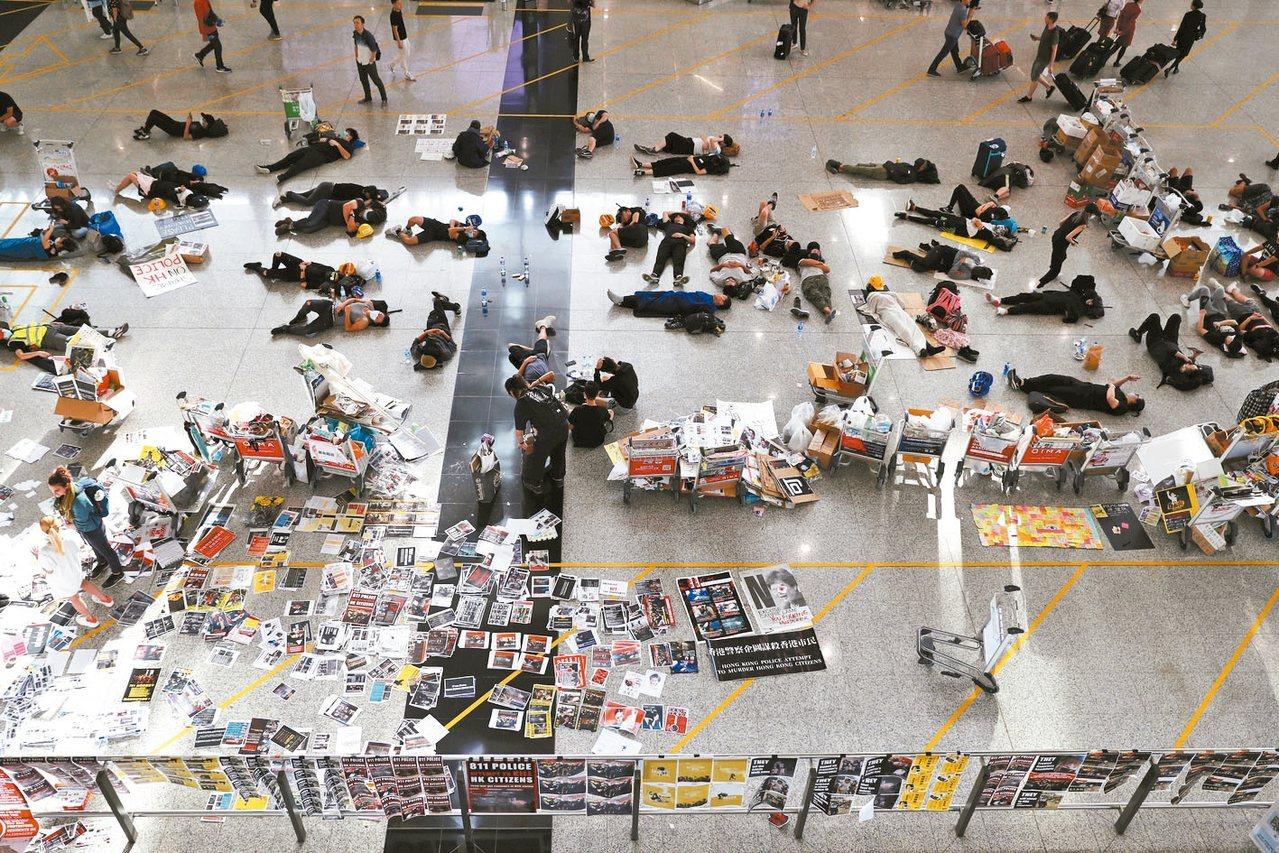 香港機場昨天因大規模靜坐癱瘓一天後,13日部分恢復運作,但仍有示威人士席地休息。...