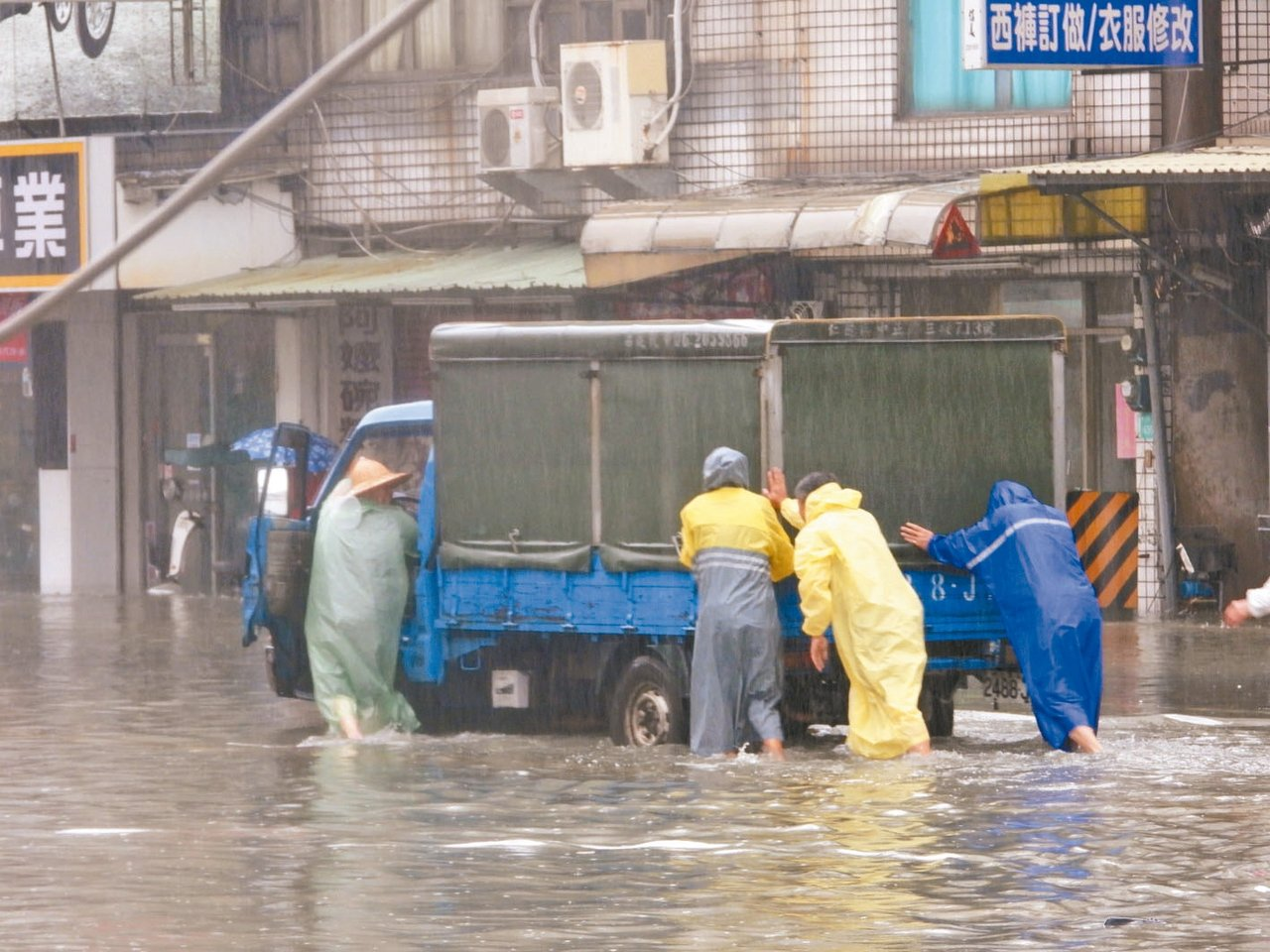 台南豪雨成災,許多汽機車輛泡水,居民一早忙著將泡水車輛推離。 記者周宗禎/攝影