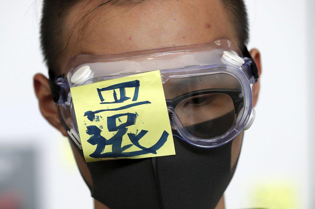 香港示威者戴上眼罩貼上「還」字紙條,要為8月11日晚間港警開槍射爆一名示威者眼睛...
