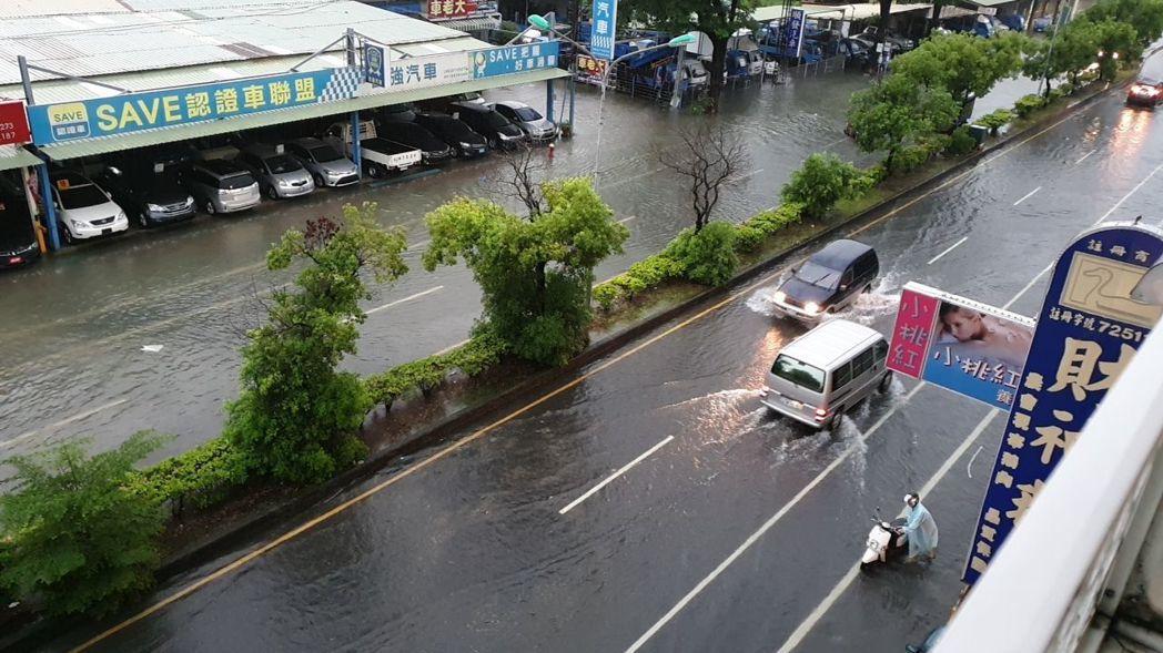台南市雷雨閃電不斷,市民一夜無眠,許多地方積水,有不少車輛經過淹水路面。圖/讀者...