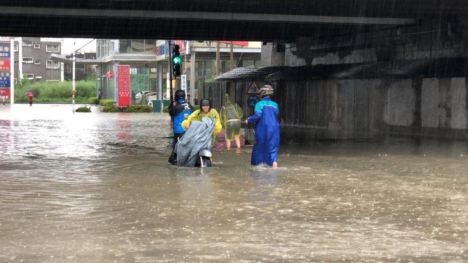 現場水深及膝,仍有民眾牽著機車或捲起褲管,通過積水路段。記者邵心杰/攝影