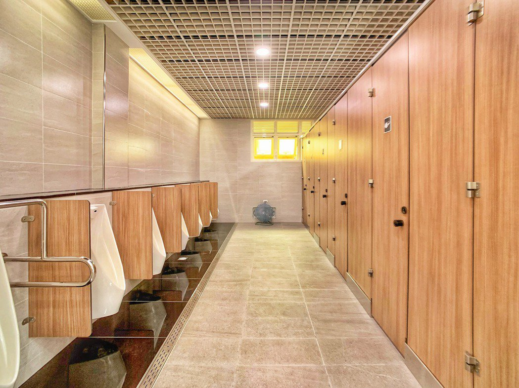 廁間隔間改為溫馨木質色調,壁面更延伸新竹火車站古蹟之灰色立面,搭配同色系石英地磚...