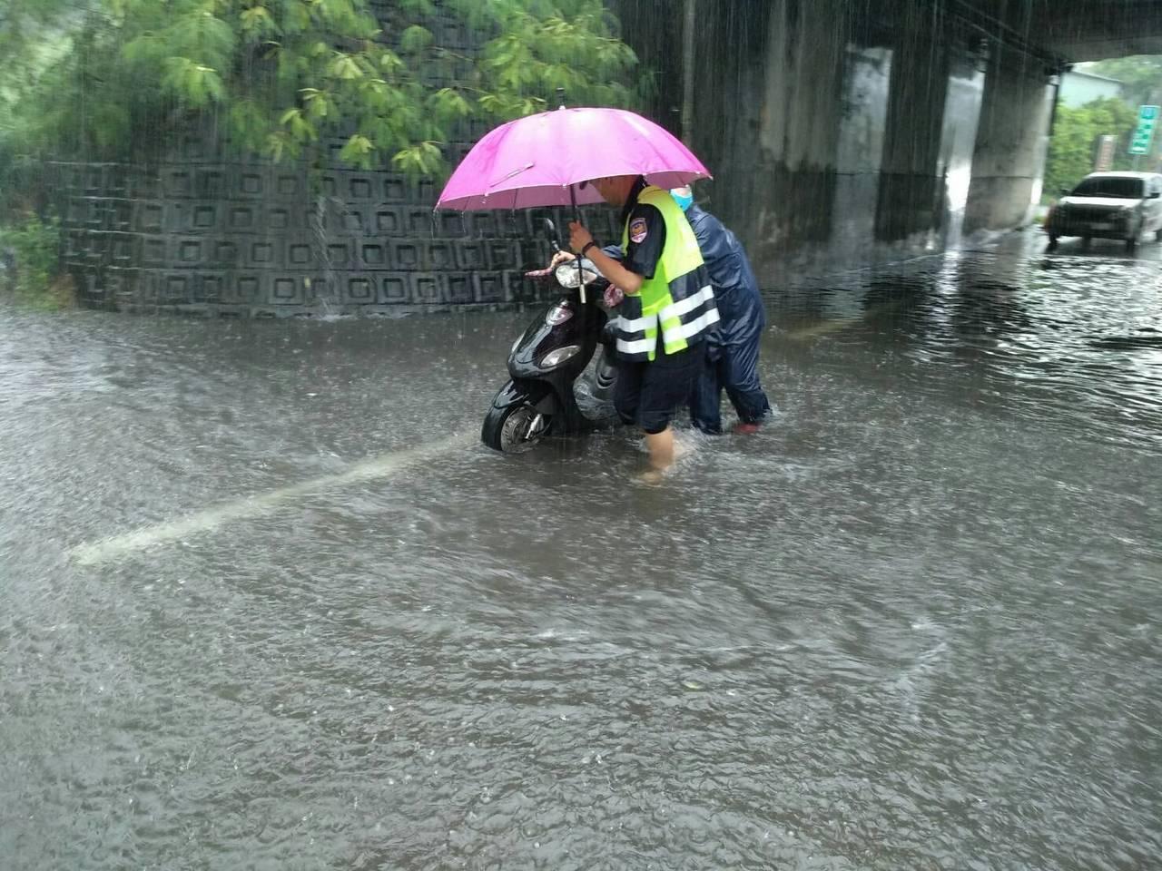 台中市區連日降雨,烏日警方協助一名阿伯推車渡過積水。圖/烏日警分局提供