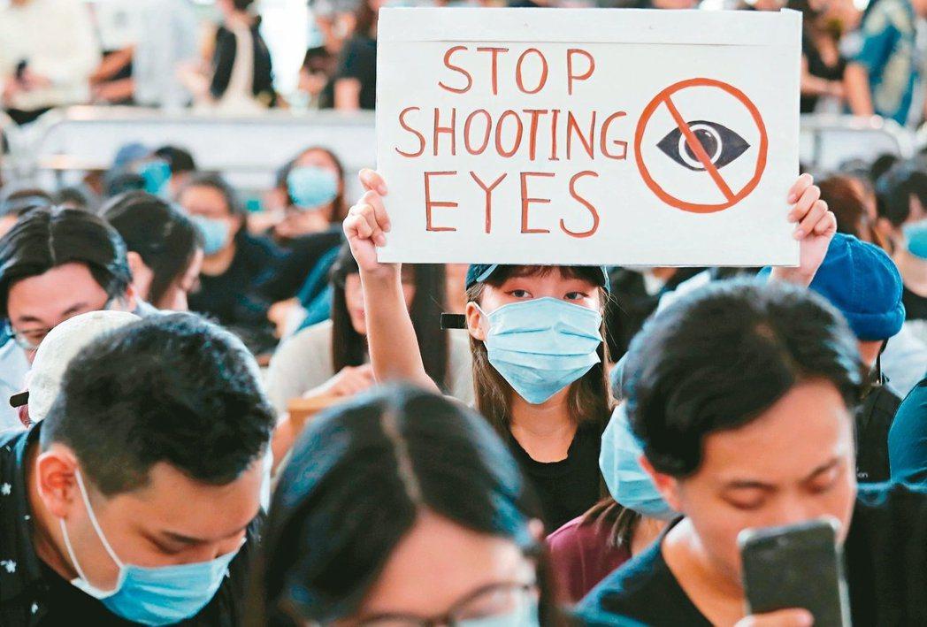 香港示威者聲援疑眼睛中彈女子,昨天發起「黑警還眼」集會,癱瘓香港機場。(路透)