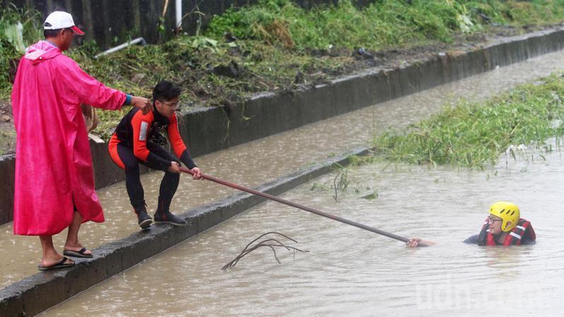高雄岡山林姓女騎士今天上午上班時疑似被大水沖走,搜救人員在現場搜尋。記者劉學聖/攝影