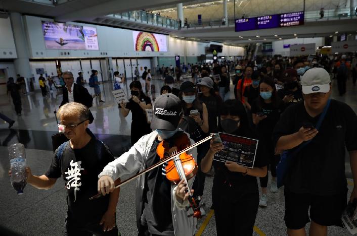現場亦有集會人士一行20多人,帶着小提琴在兩邊的接機大堂遊走,並唱着悲慘世界的《Do you hear the people sing》。(香港01)
