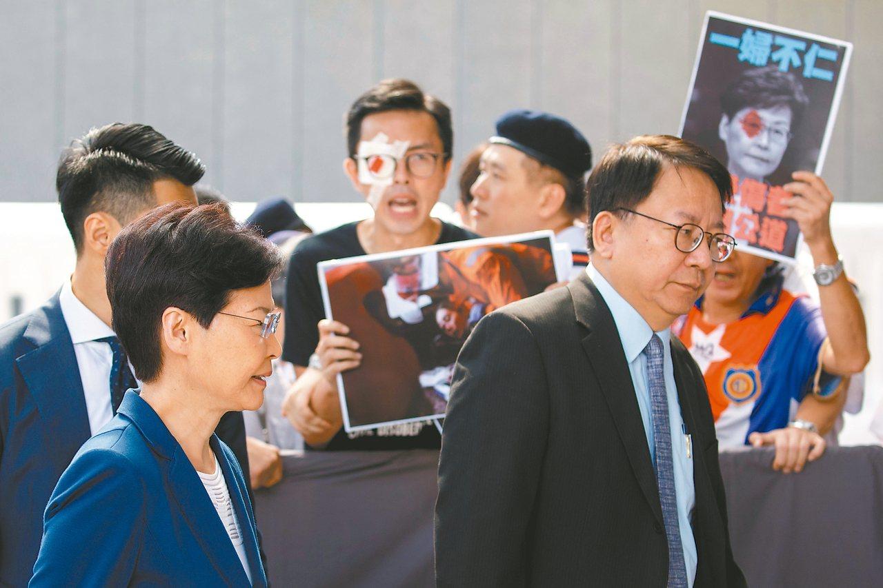 香港特首林鄭月娥(左)在行政長官辦公室外遇上示威者。 (路透)