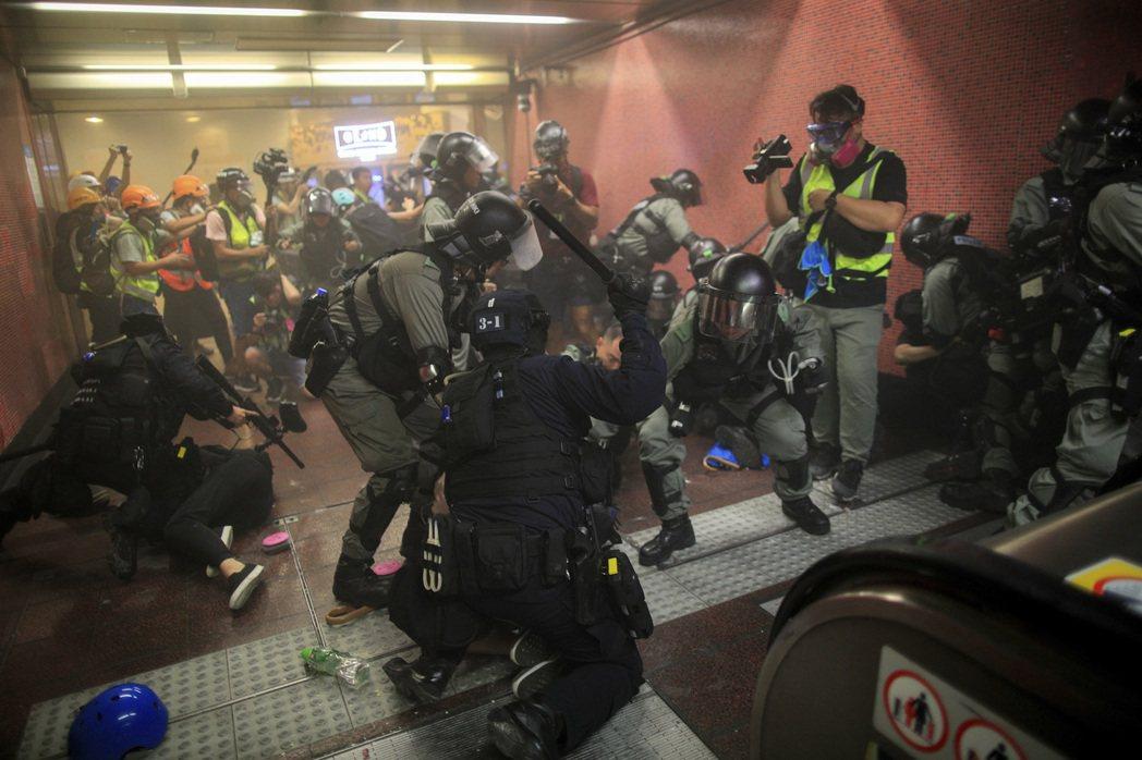 8月11日,網路上傳播著一段影片,顯示警察沿著自動扶手電梯,亂棍狂毆示威者。 圖/美聯社