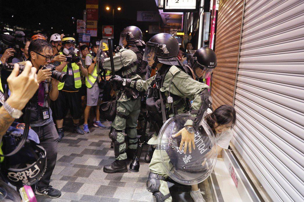 在抗爭現場,隨時都會看到記者及抗爭者拿著手機,記錄現場狀況。 圖/美聯社