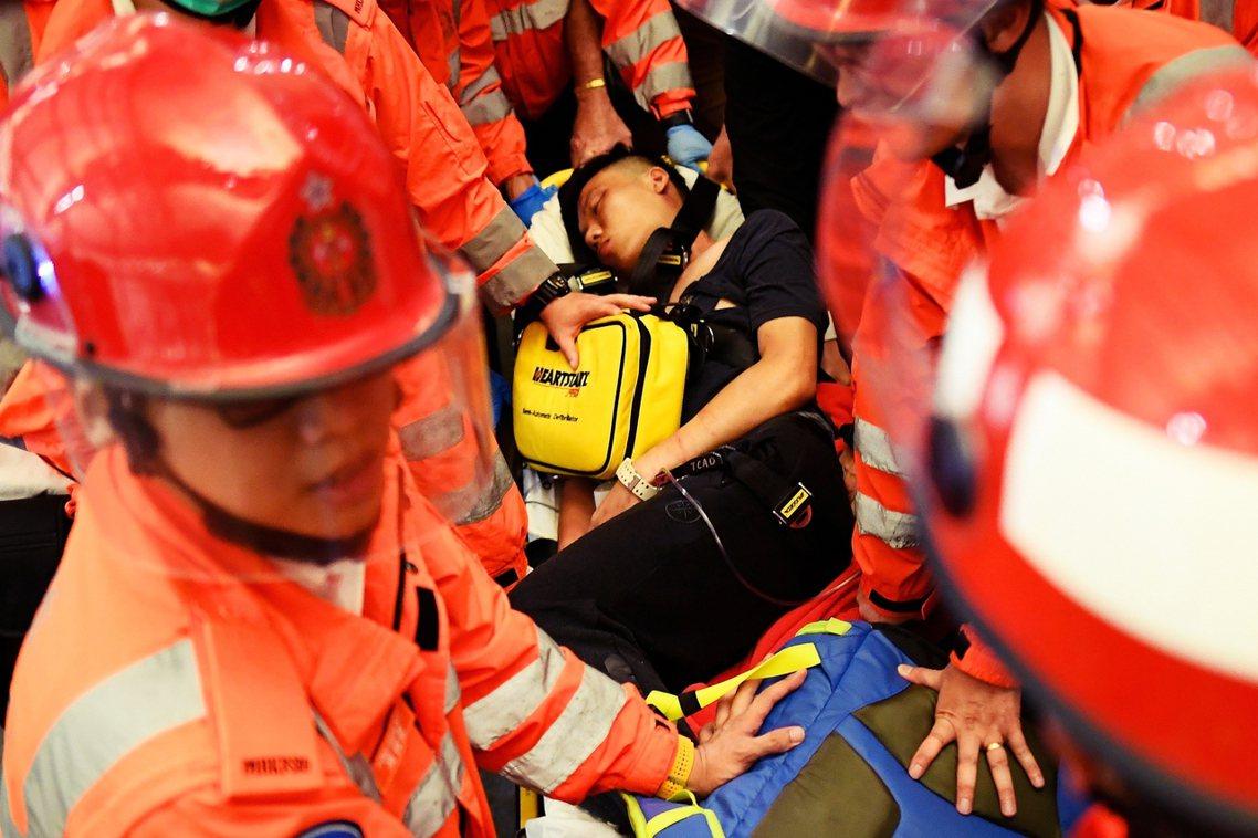 圖為一名被質疑違中國臥底混入示威群眾的男子,受傷並被醫護人員送離機場。 圖/法新...