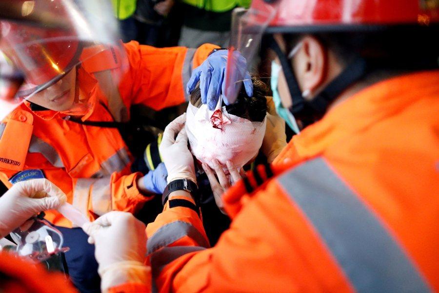 前線女示威者(一說是救護人員)右眼中彈。攝於8月11日,香港。 圖/路透社