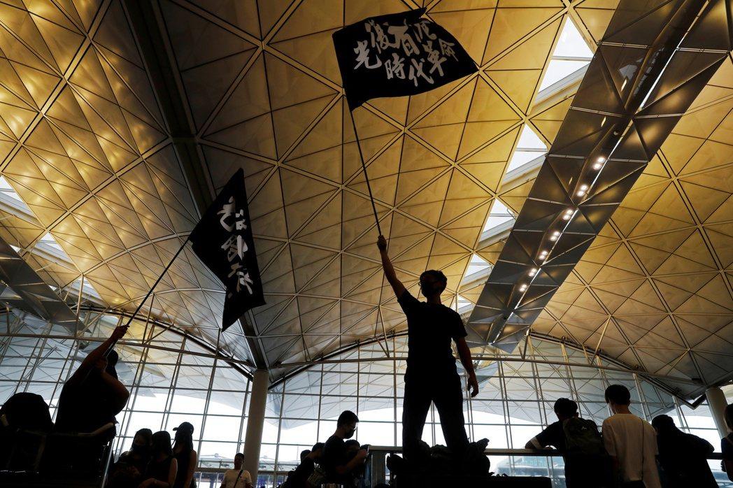 攝於8月12日,抗爭者在機場舉著「光復香港、時代革命」旗幟。 圖/路透社