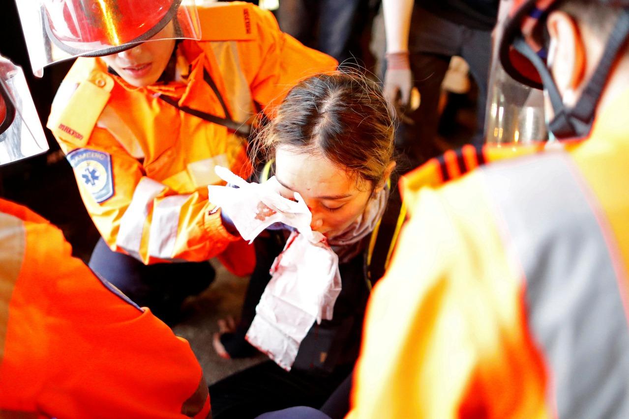 攝於8月11日,一名女子遭警方的布袋彈擊中。 圖/路透社
