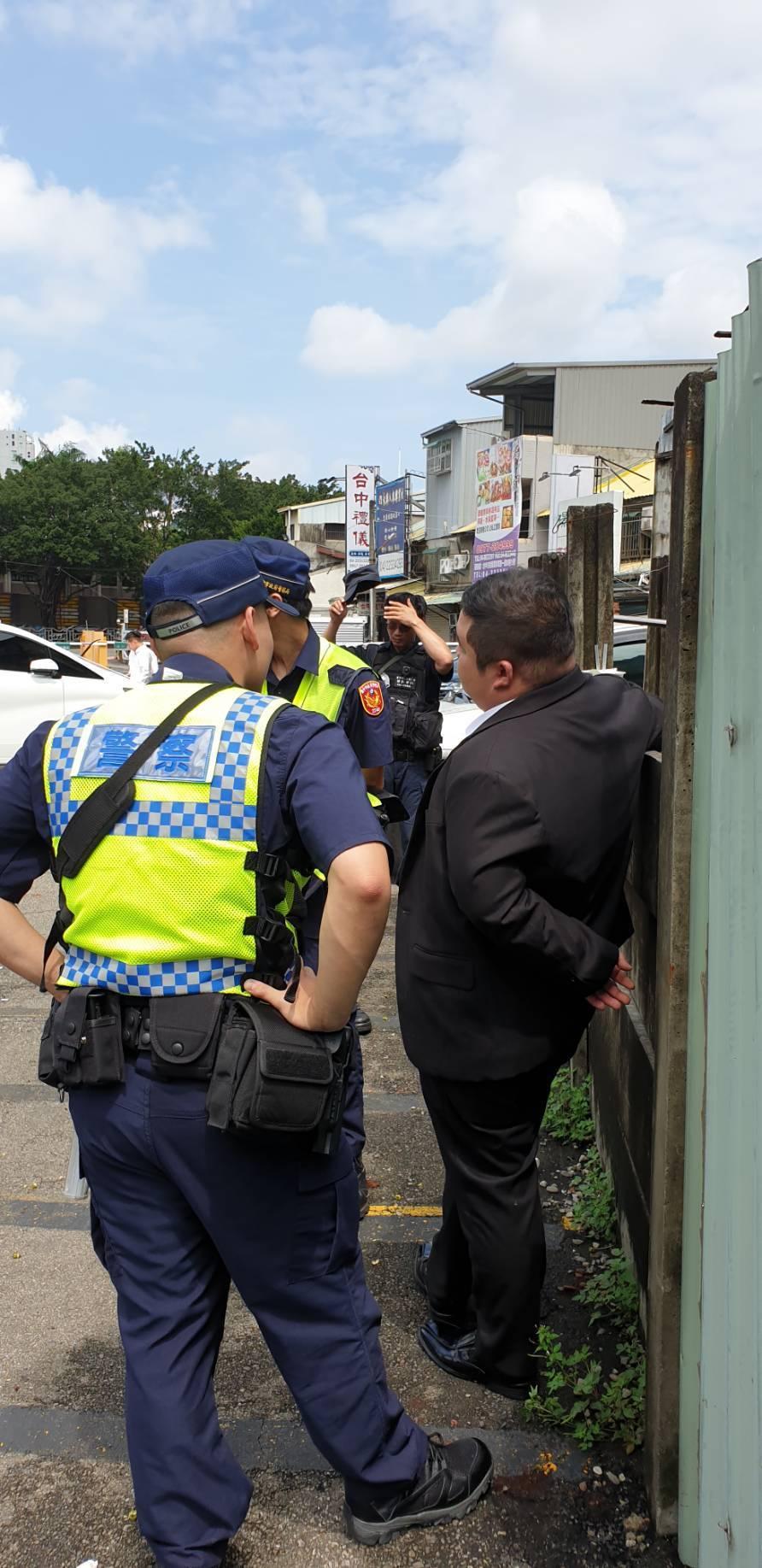 警方今早在台中市立殯儀館對面停車場查獲一名藍姓男子(右)遭詐欺通緝,警方已帶回所...