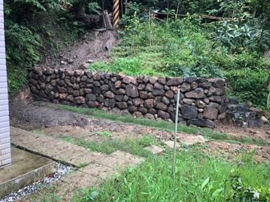 經過水保技師的指導,陳先生的土地完成1.2公尺高的砌石擋土牆。圖/新北市農業局提...