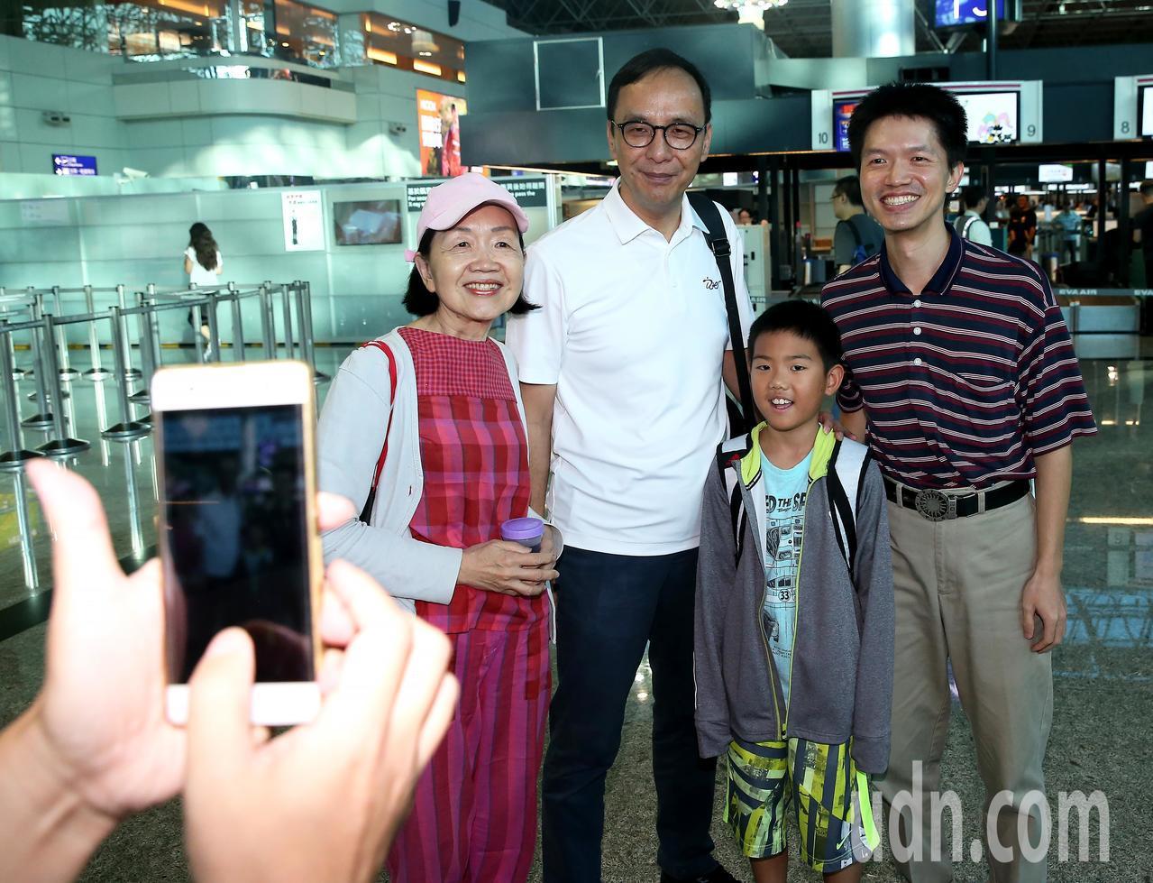 國民黨前主席朱立倫(右三)14日晚間搭機前往美國訪問,登機前應旅客要求合影留念。...