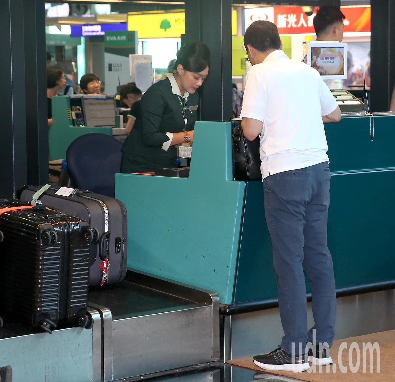 國民黨前主席朱立倫(右)14日晚間搭機前往美國訪問,在長榮航空公司櫃台辦理登機報...