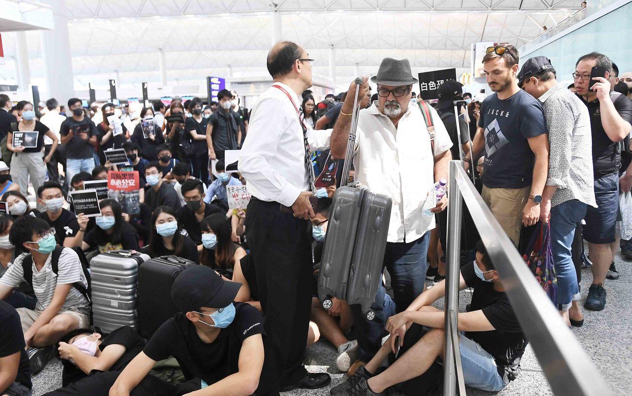 8月13日下午,大批示威者以機場手推車等堵塞香港國際機場1號客運大樓旅客登機行段...