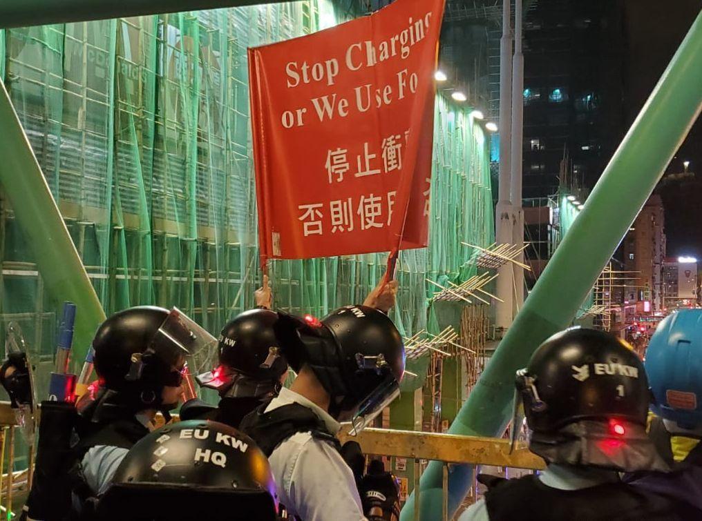 防暴警察舉紅旗,要求示威者停止衝擊。圖:星島日報網站