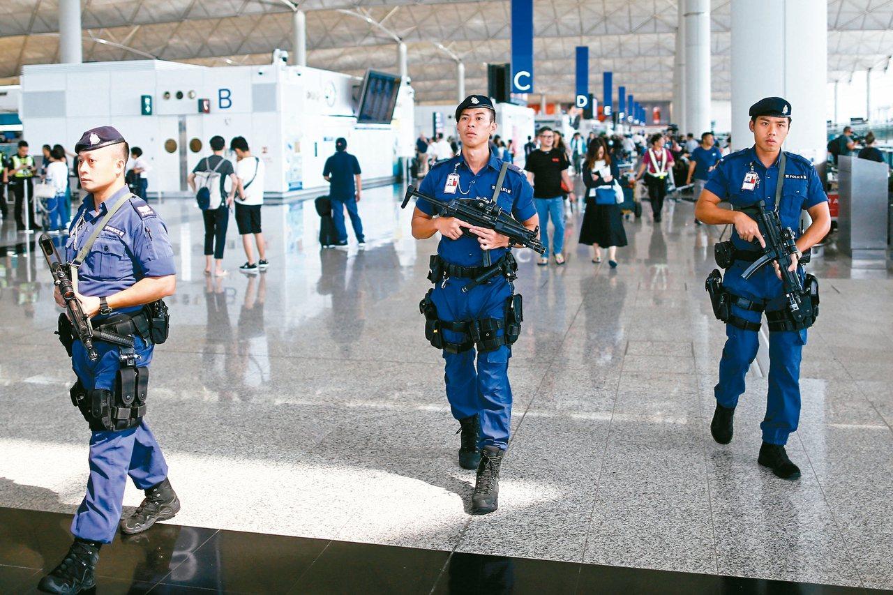 香港警察十四日荷槍實彈在機場出境大廳巡邏。 (路透)