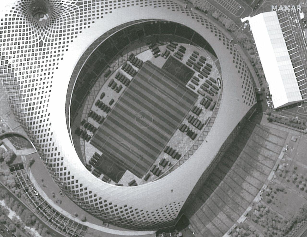 從空拍的衛星照片可清楚看到,臨近香港的深圳春繭體育館內已停滿軍用車輛。這張照片是...